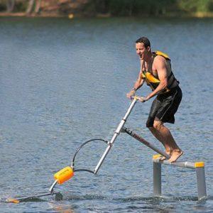 Um homem praticando o esporte aquaskipper no lago, indo em direção ao lado esquerdo da imagem.