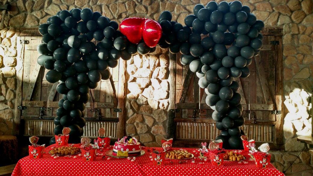 mesa decorada para aniversário temático da Minnie. Ao fundo, coluna de balões com formato das orelhinhas.