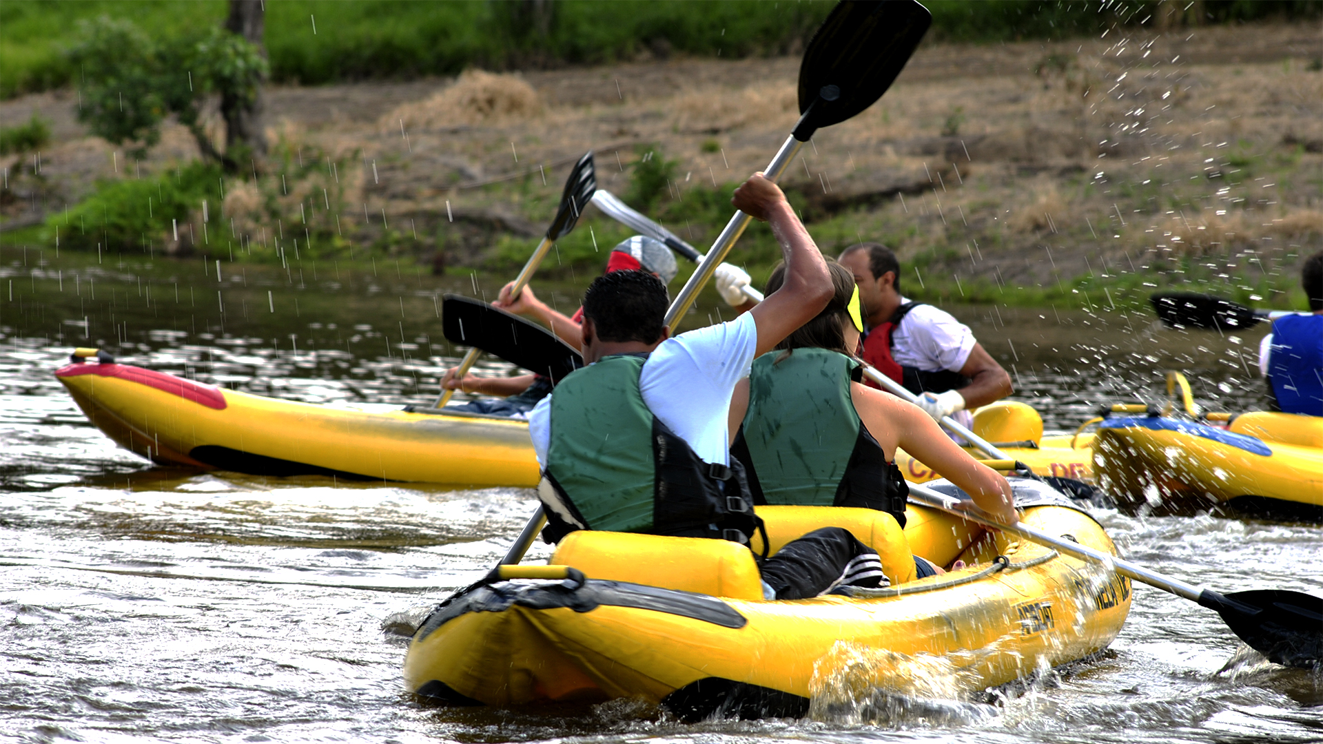 Duas pessoas na canoa indo em direção ao canto superior direito da imagem. Ao fundo é possível ver outra canoa com duas pessoas indo em direção ao lado esquerdo da foto. Existe movimentação e respingos de água devido à ação de remar.