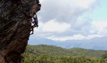 No lado esquerdo da imagem é possível ver uma pessoa, de lado, escalando uma parede rochosa. No resto da imagem é possível ver o céu e várias árvores