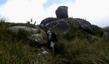 Pessoas subindo uma montanha, andando entre pedras.